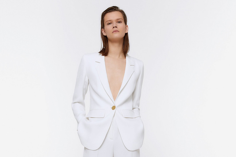 Girl wearing a white suit with one gold button