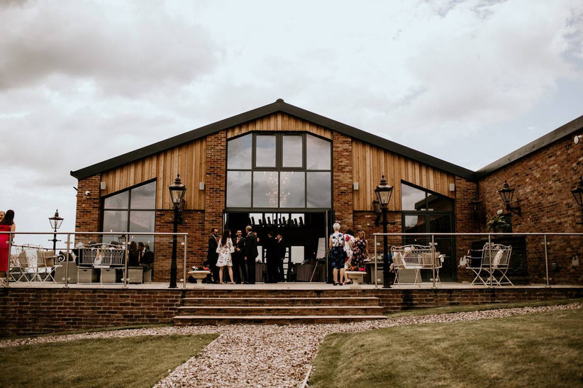 Wedding guests mingle outside a wooden building with open patio doors