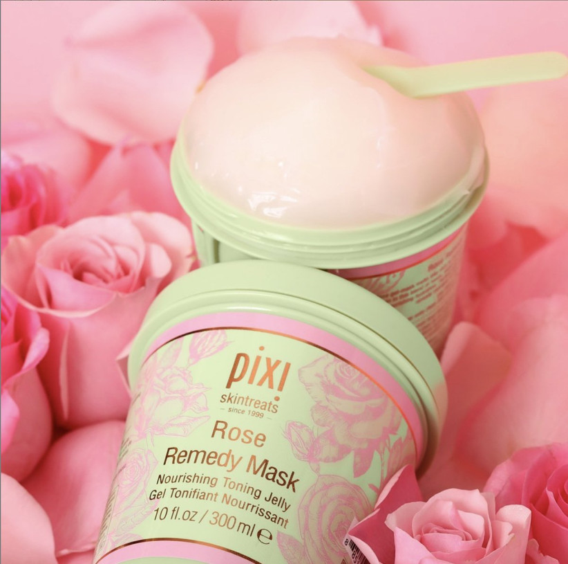 Close-up of a tub of Pixi Rose Remedy Mask on a bed of pink roses