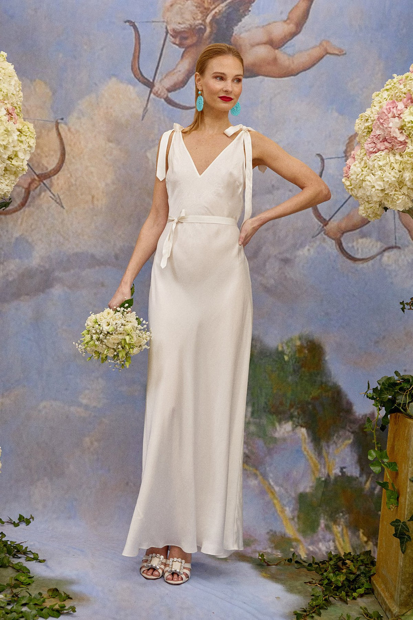 Girl wearing a silk wedding dress with bow shoulder details
