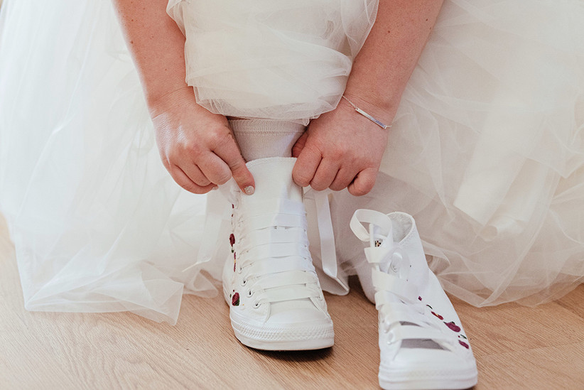 Becky putting on white wedding trainers