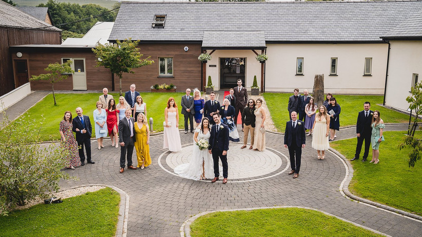 Socially distanced wedding photo of the bride, groom and their guests
