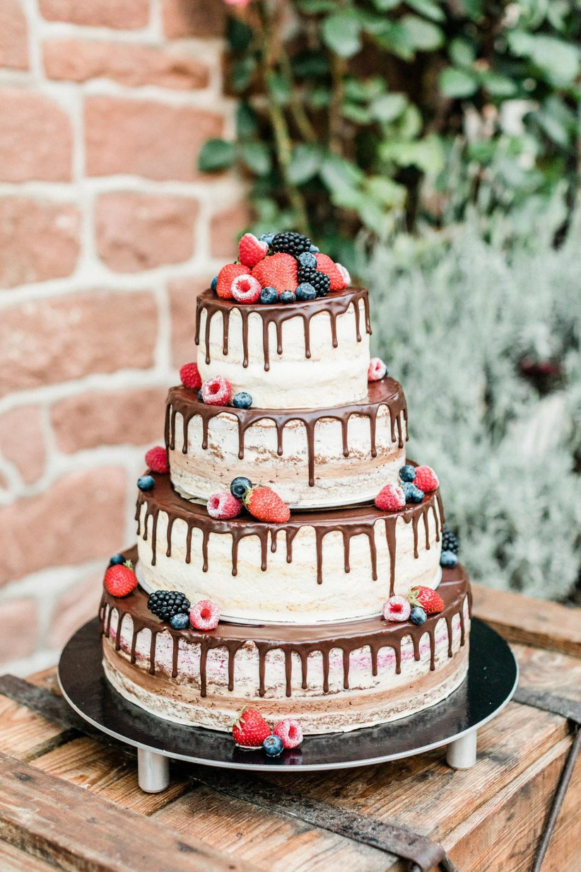 Four tiered rustic wedding cake with chocolate drips and berries