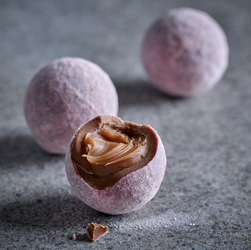 Pink dusted champagne truffles on a slate surface