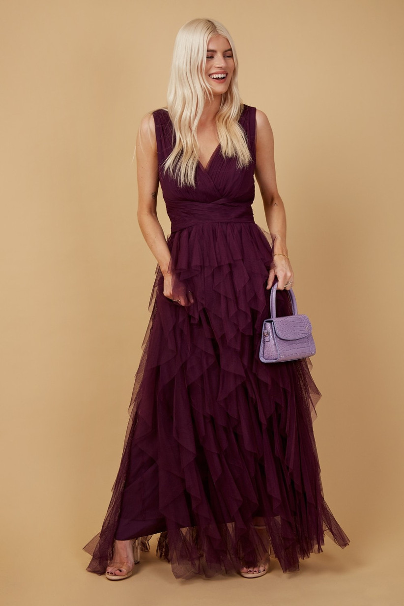 Girl wearing a mesh ruffle plum maxi dress holding a lilac bag