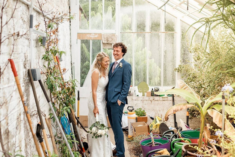 Bride and groom laughing in a greenhouse