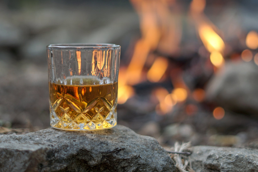 Etched crystal glass full on whisky balanced on a rock with a fire behind