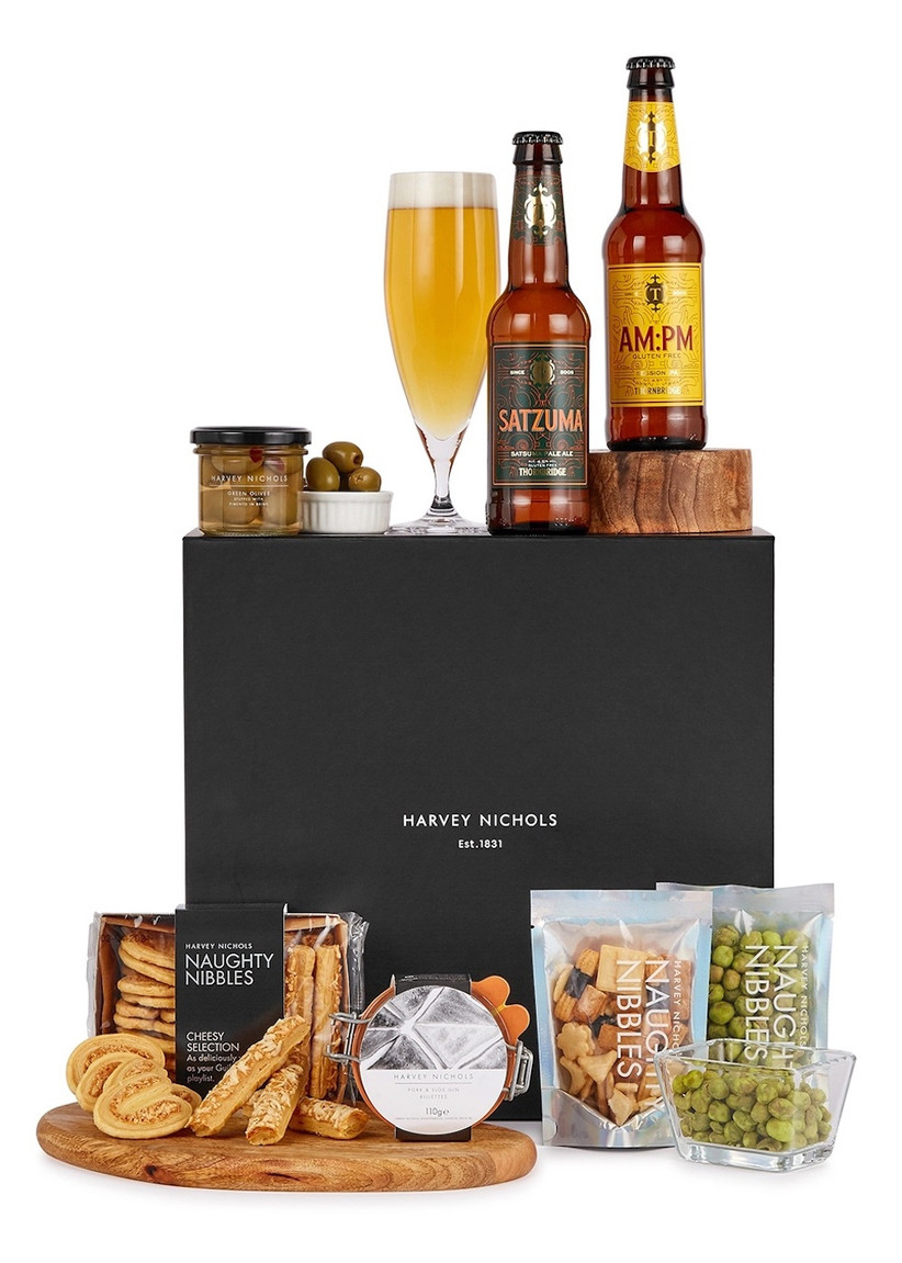 A black gift box with bottles of beer and a jar of green olives on top of it and cheesy snacks and Japanese crackers on a wooden board at the bottom