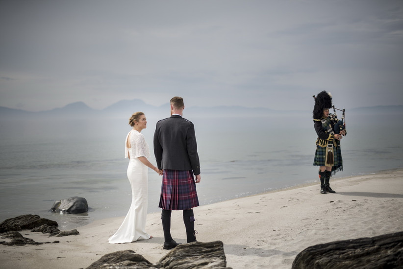 Bride in a white wedding dress and groom in a kilt standing on a beach with a bagpiper in traditional dress