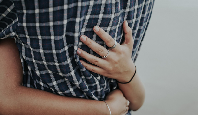 Woman hugging her partner in a gingham shirt with two silver rings on her first and second fingers