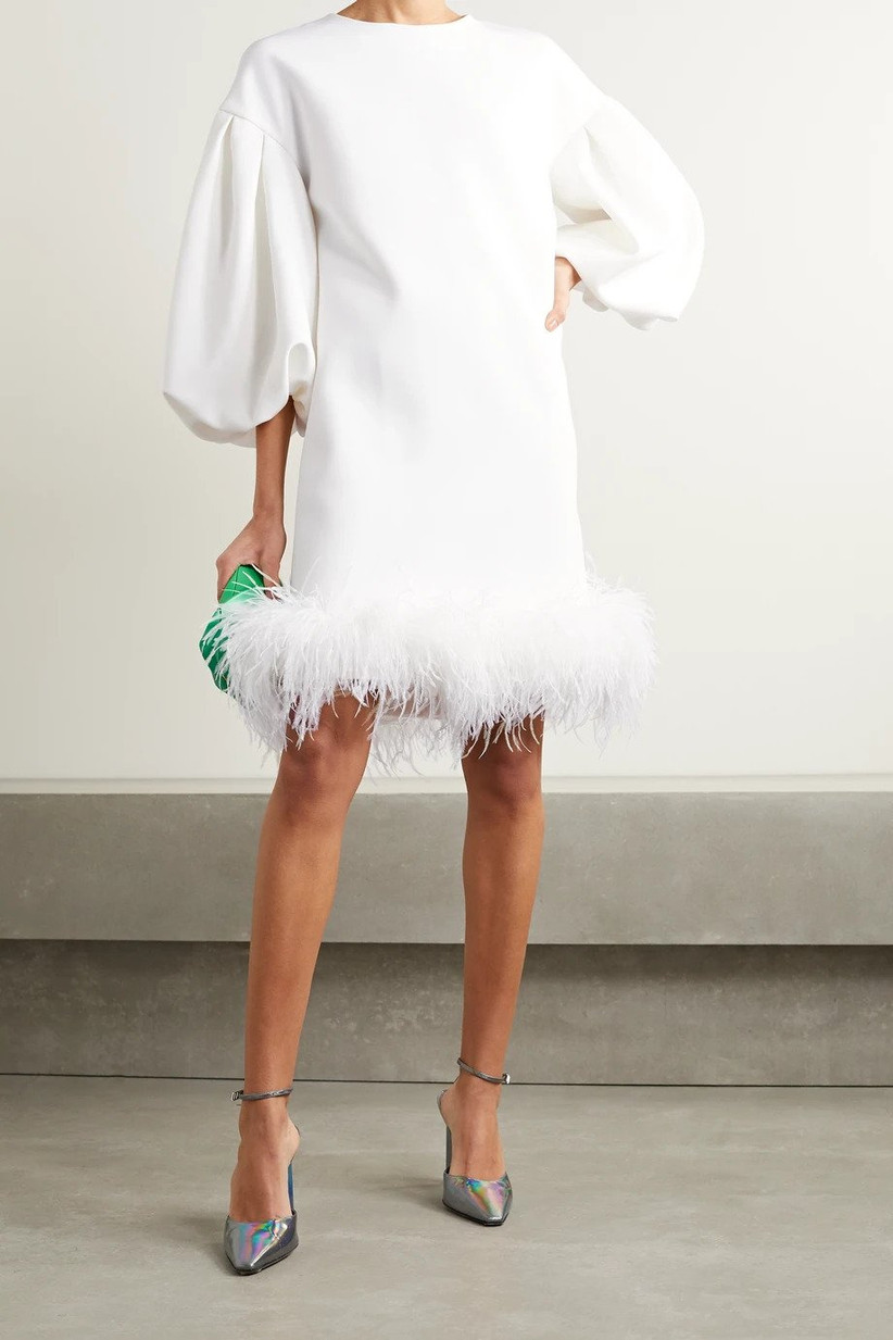 White short wedding dress with feather trim at the hem