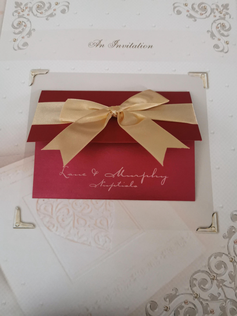 Red wedding invitation tied with a gold bow on a cream background