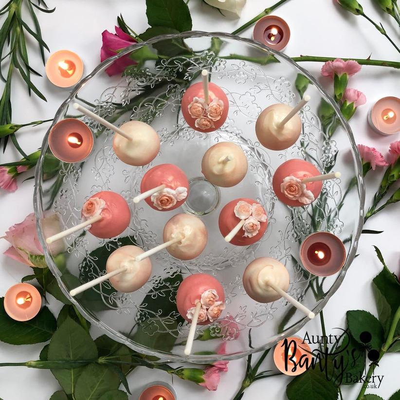 Pink and white floral cake pop wedding favours on a cake plate