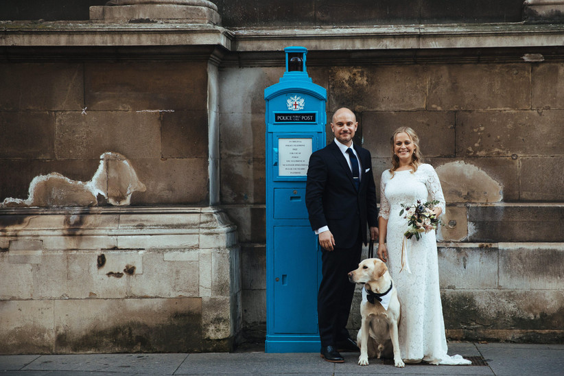 Bride and groom standing beside a bright blue police box with their pet labrador on their wedding day