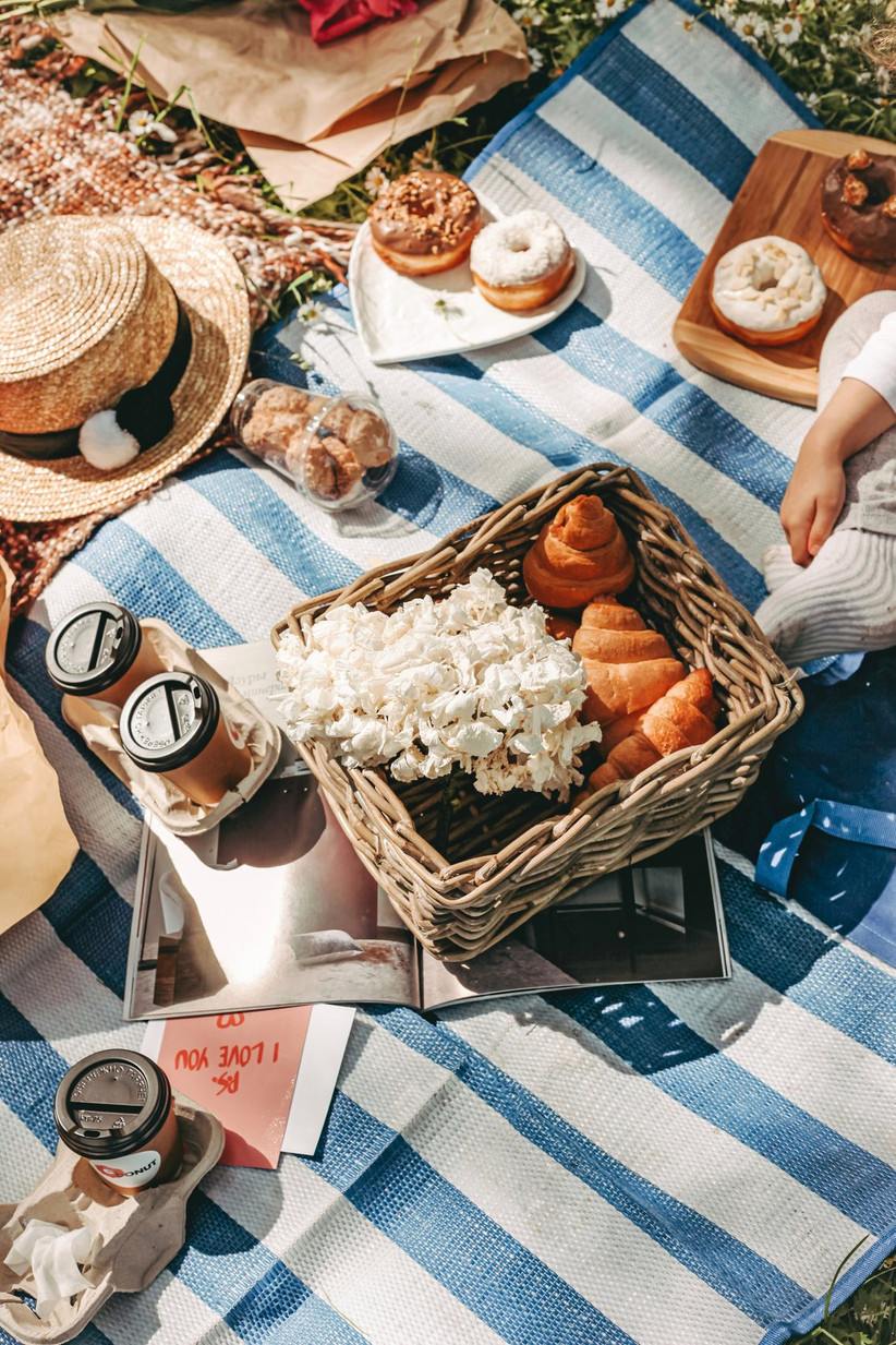 Striped rug on grass with a woman's leg next to a basket full of pastries and flowers, wooden boards with doughnuts, two coffees and a straw sunhat