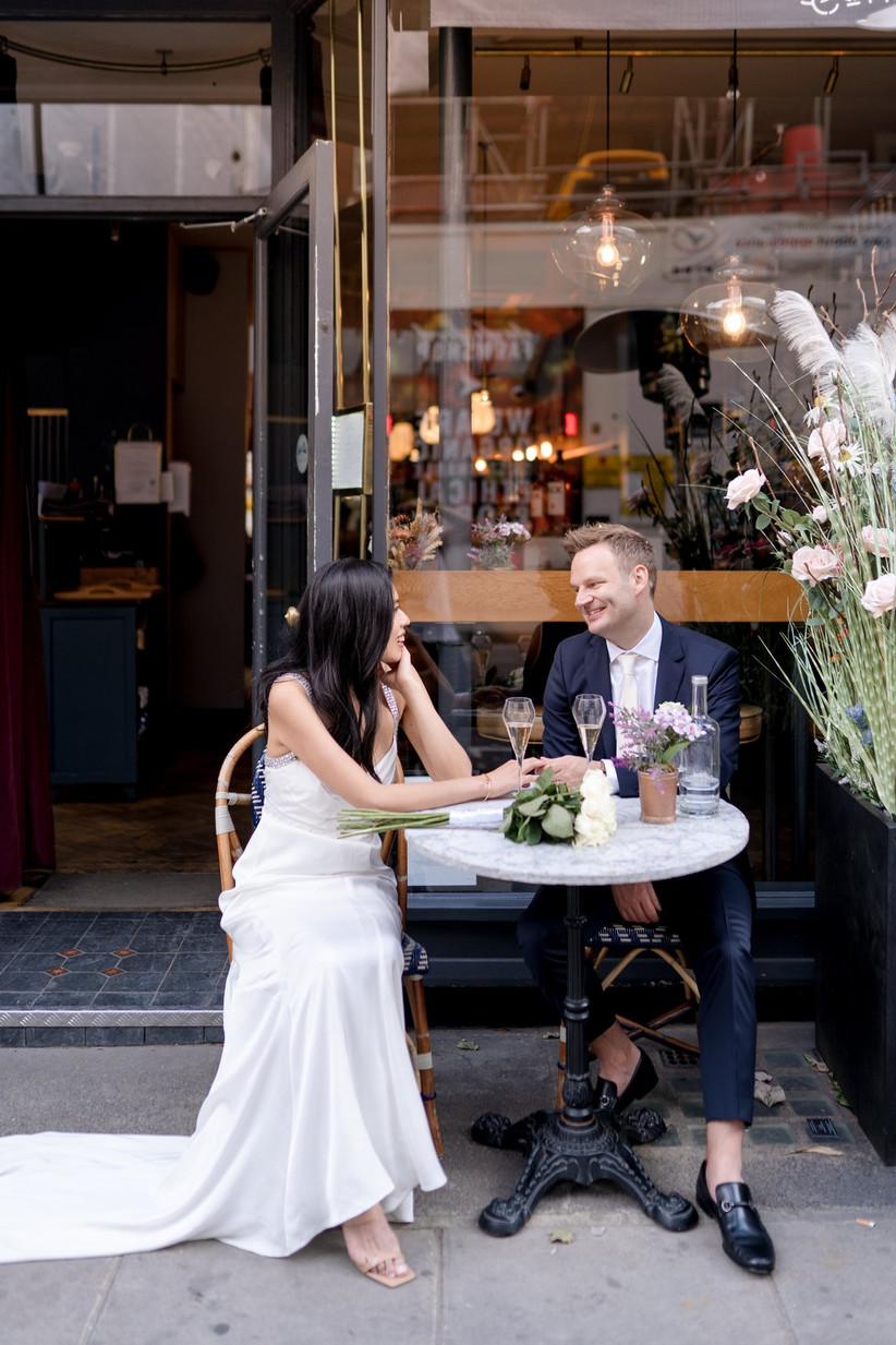 Bride and groom sitting at a table outside a London restaurant