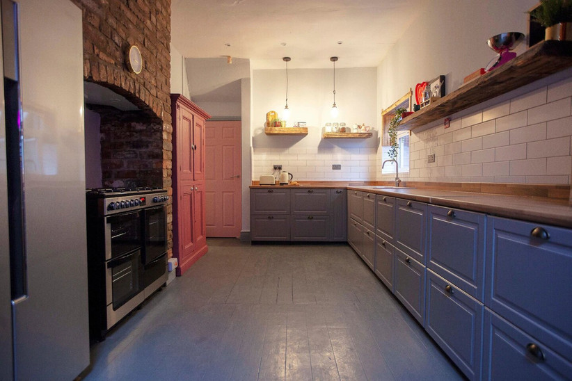 Kitchen with grey cupboards and pink door