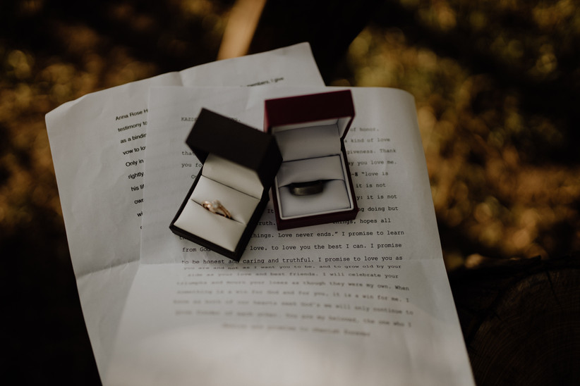 Two open ring boxes with a gold and diamond ring and dark metal wedding ring on top of two sheets of paper featuring typed out wedding vows