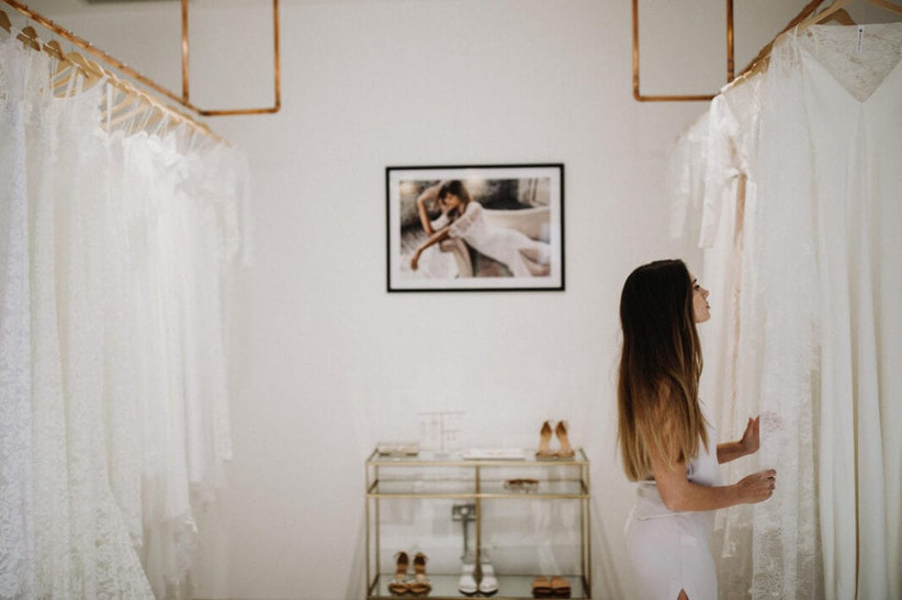 A female stylist looks at rows of wedding dresses hanging from racks in the Grace Loves Lace London showroom