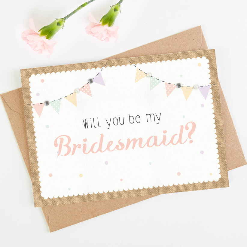 White card edged with bunting with will you be my bridesmaid written in the middle