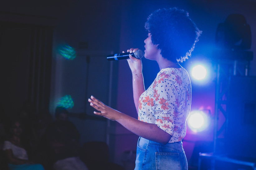 Woman with an afro wearing a flowery top and denim shorts singing into a microphone with disco lights behind her