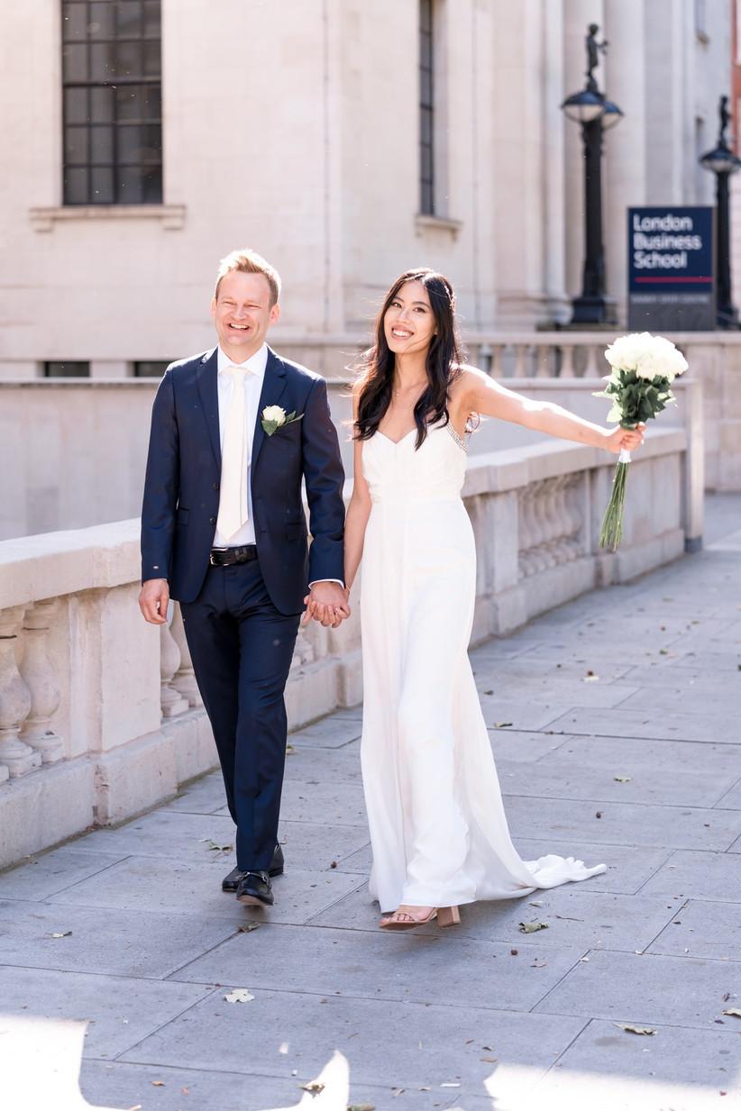 Bride and groom walking along a London street
