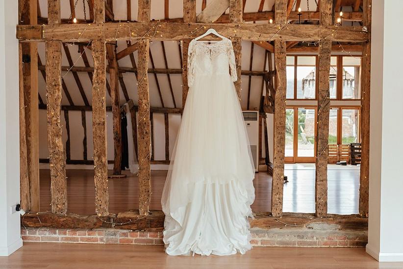 White wedding dress hanging from oak beams