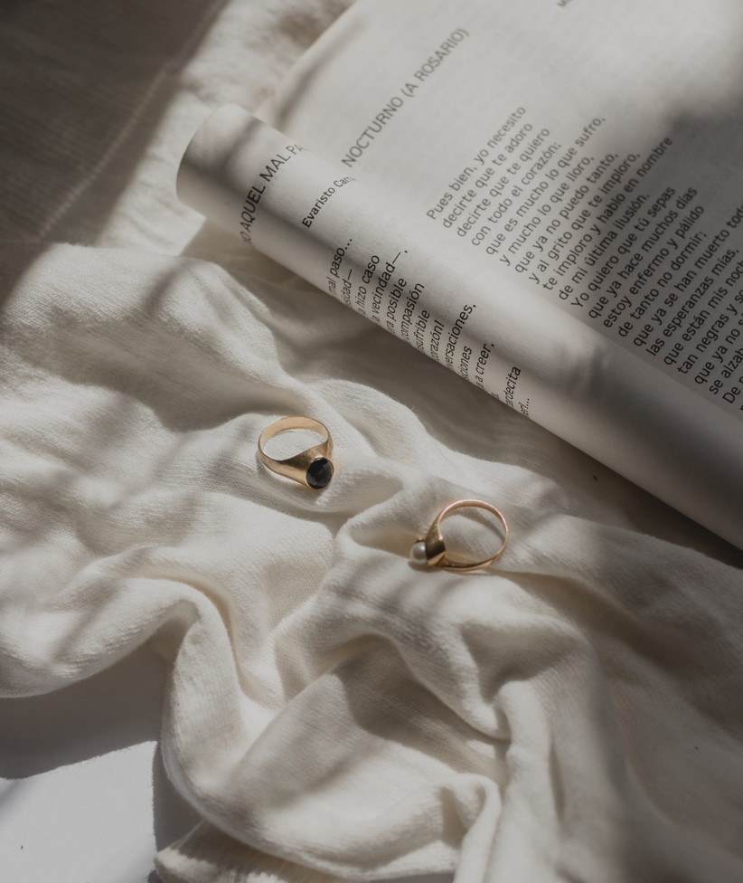 A gold masculine ring with a dark blue stone at the centre next to a contemporary gold women's pearl ring on a white sheet next an open book