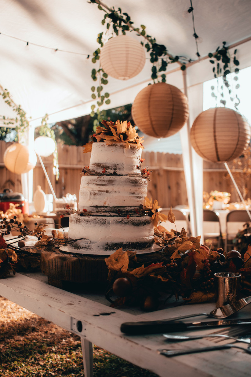 Cream semi naked three tiered cake borded with red flowers with sunflowers on top on an autumnal style table with ochre paper lanterns behind