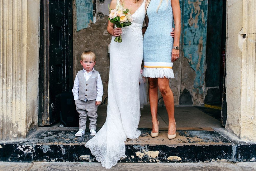 Bride standing in a doorway with a female in a blue dress and a little boy in a suit