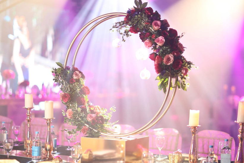 Gold hoops decorated with pink and red flowers on a table at a wedding reception