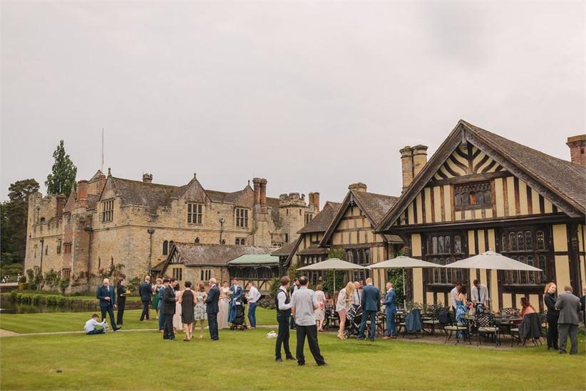 Wedding guests mingle next to a castle venue