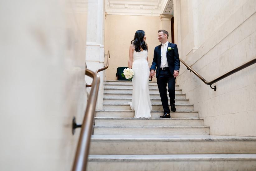 Bride and groom walking down stairs inside