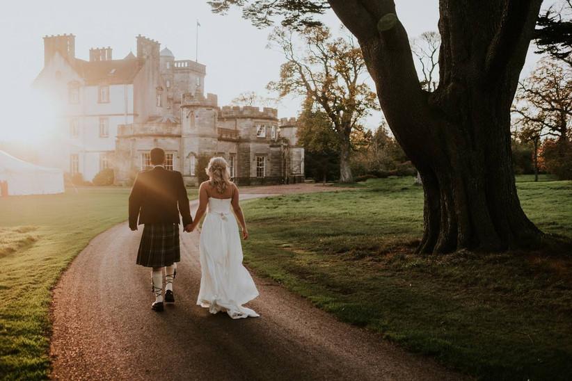 Bride and groom hold hands walking towards a castle wedding venue