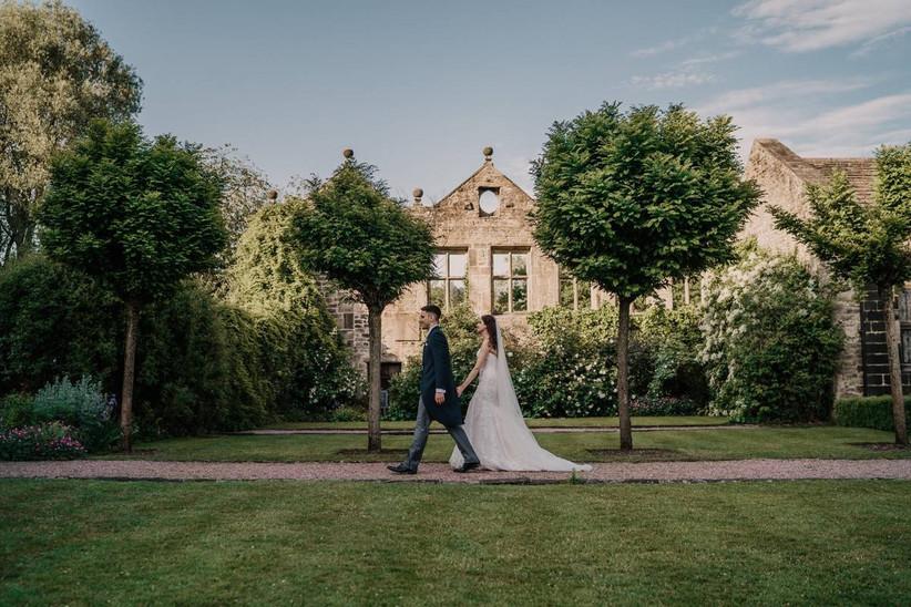 Bride and groom hold hands walking around wedding grounds