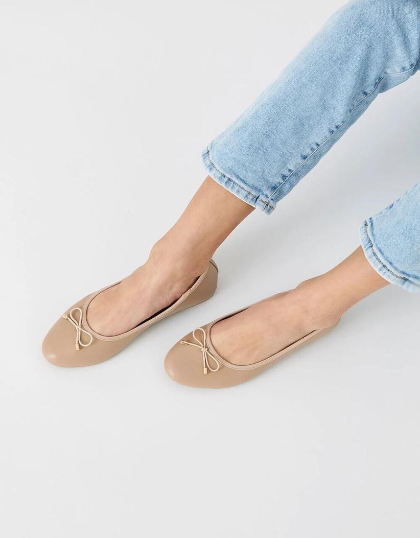 Model wearing flat bridal shoes