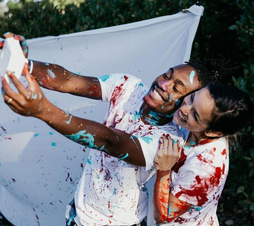 Paint covered couple taking a photo