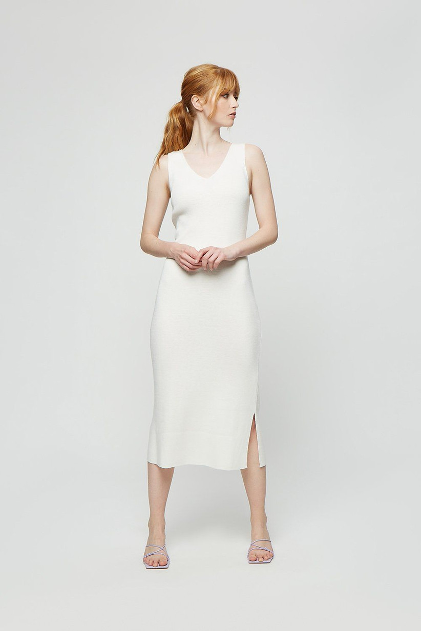 Model wearing a simple white bridesmaid dress