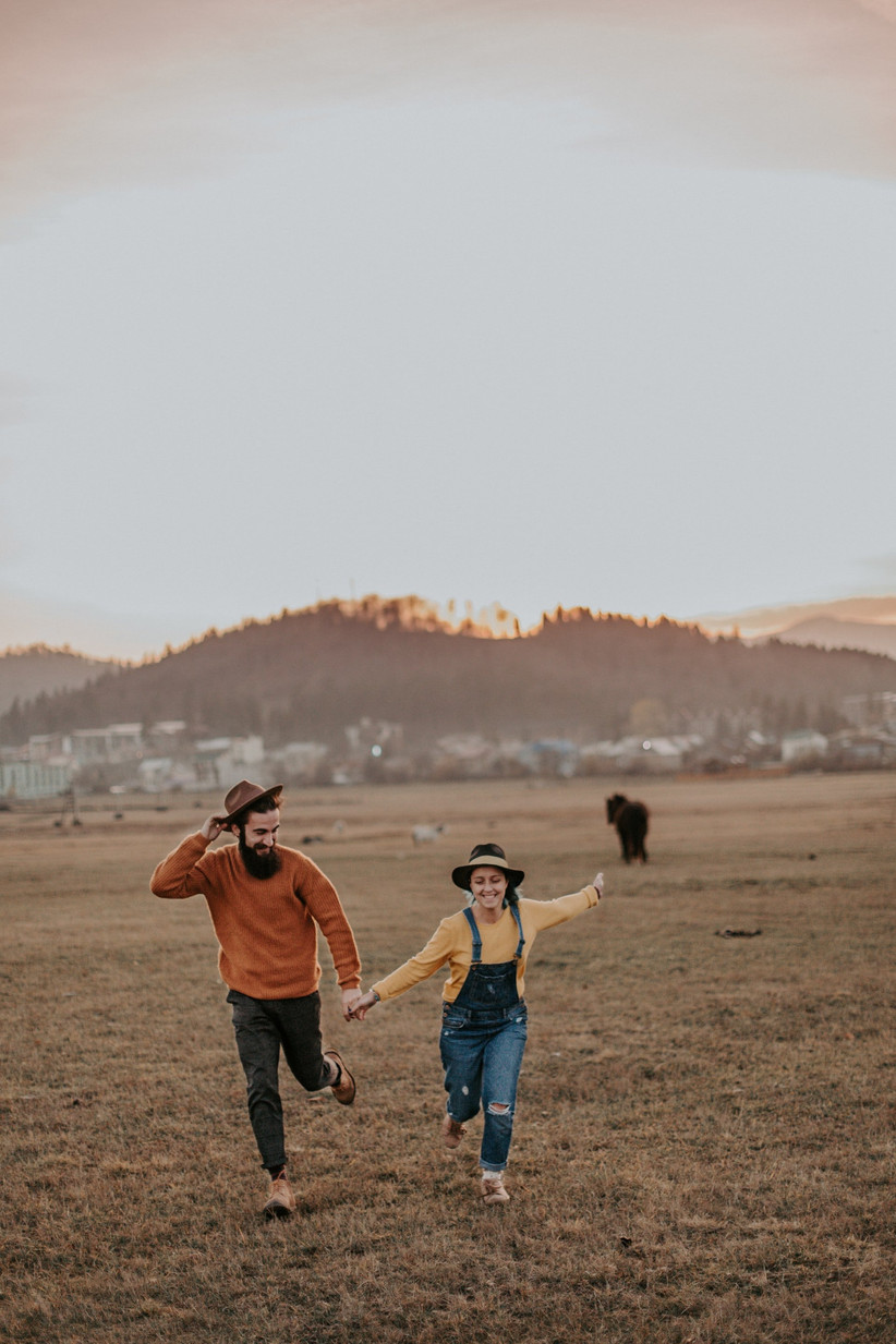 Heterosexual couple holding hands and running though a field looking happy