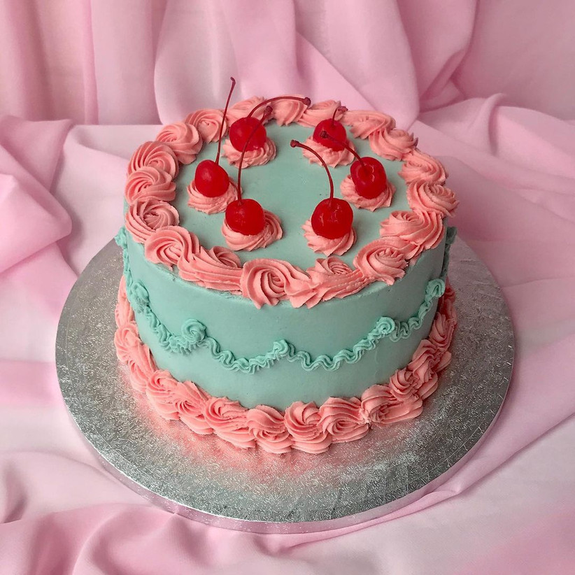 Blue and pink cake with swirls and cherries