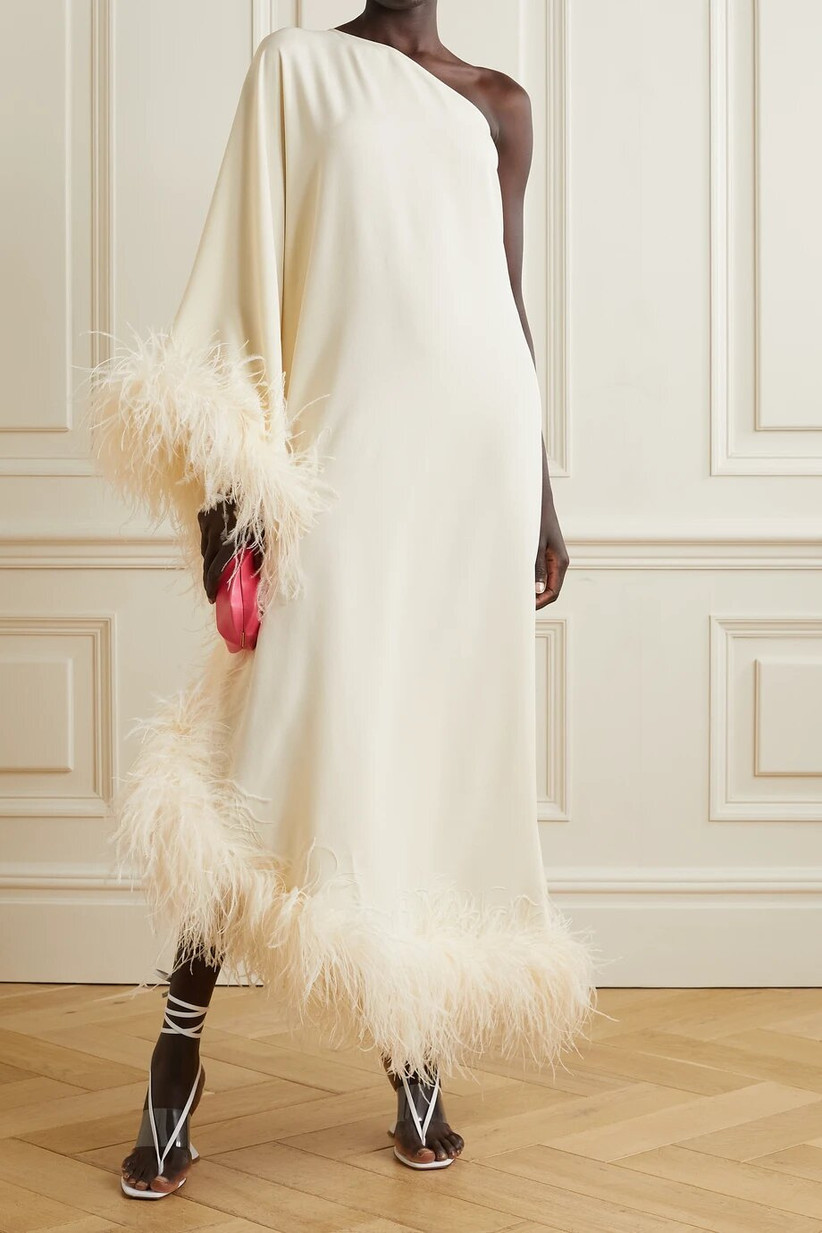 Model wearing a caped feather trim wedding dress
