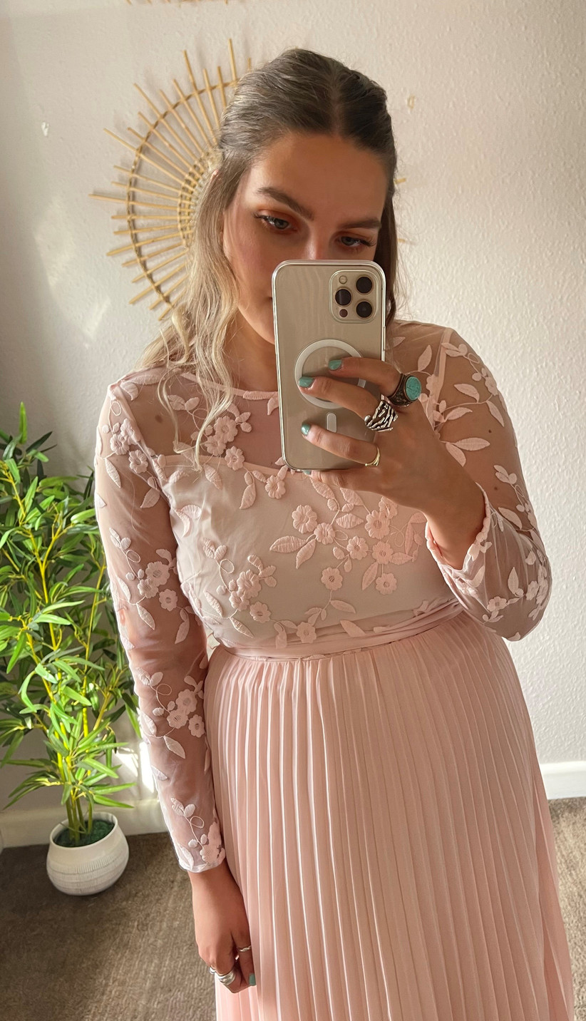 Model wearing a pink pleated long sleeved bridesmaid dress