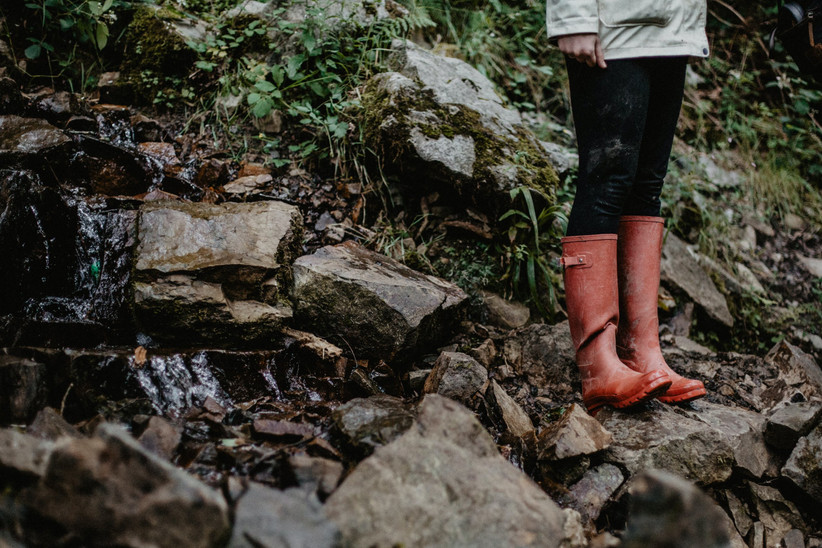 White woman in a light green parka, black leggings and red wellies standing on a rocky hillside in the rain