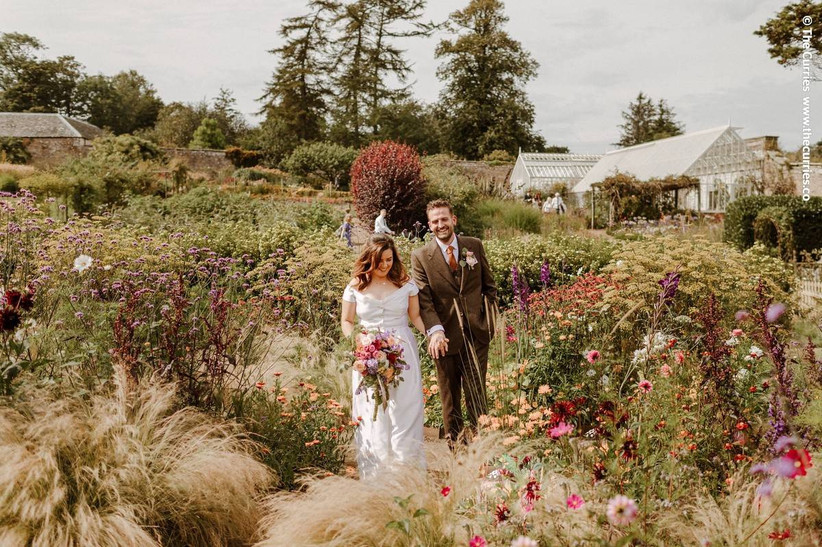 Bride and groom in a flower filled garden