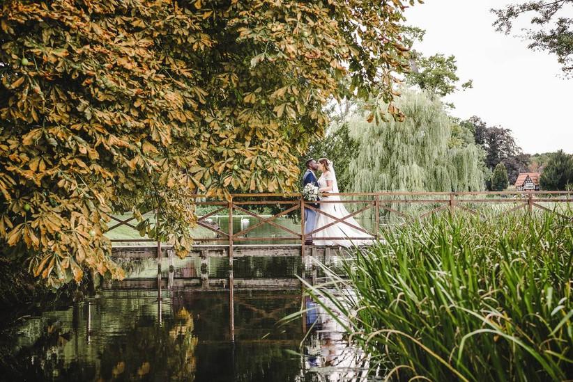 Bride and groom kiss on a bridge over a lake