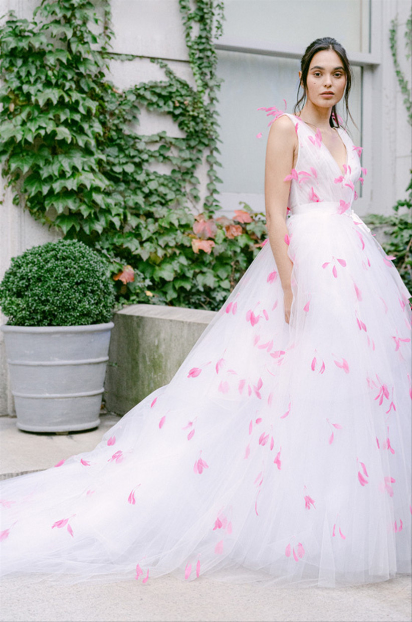 Model wearing a pink feather adorned wedding dress