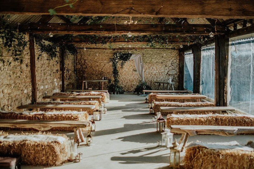 Wedding ceremony in a barn with hay bale seats