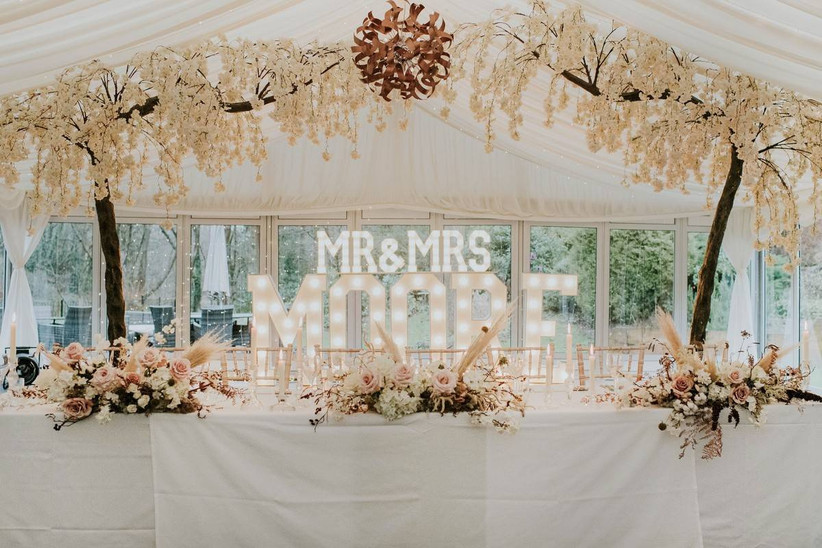 Top table at wedding decorated with white flowers and trees