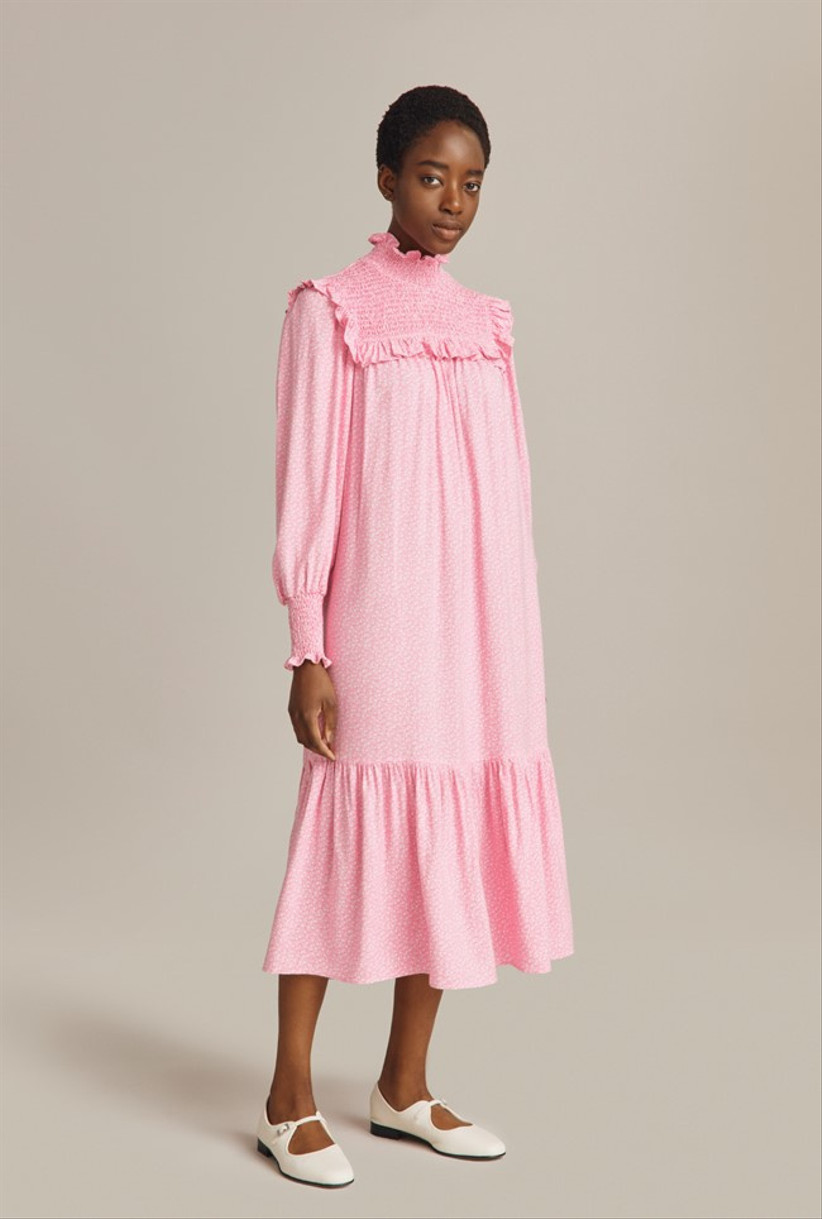 Model wearing a pink collared wedding guest dress