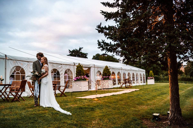 Bride and groom stand outside a wedding marquee